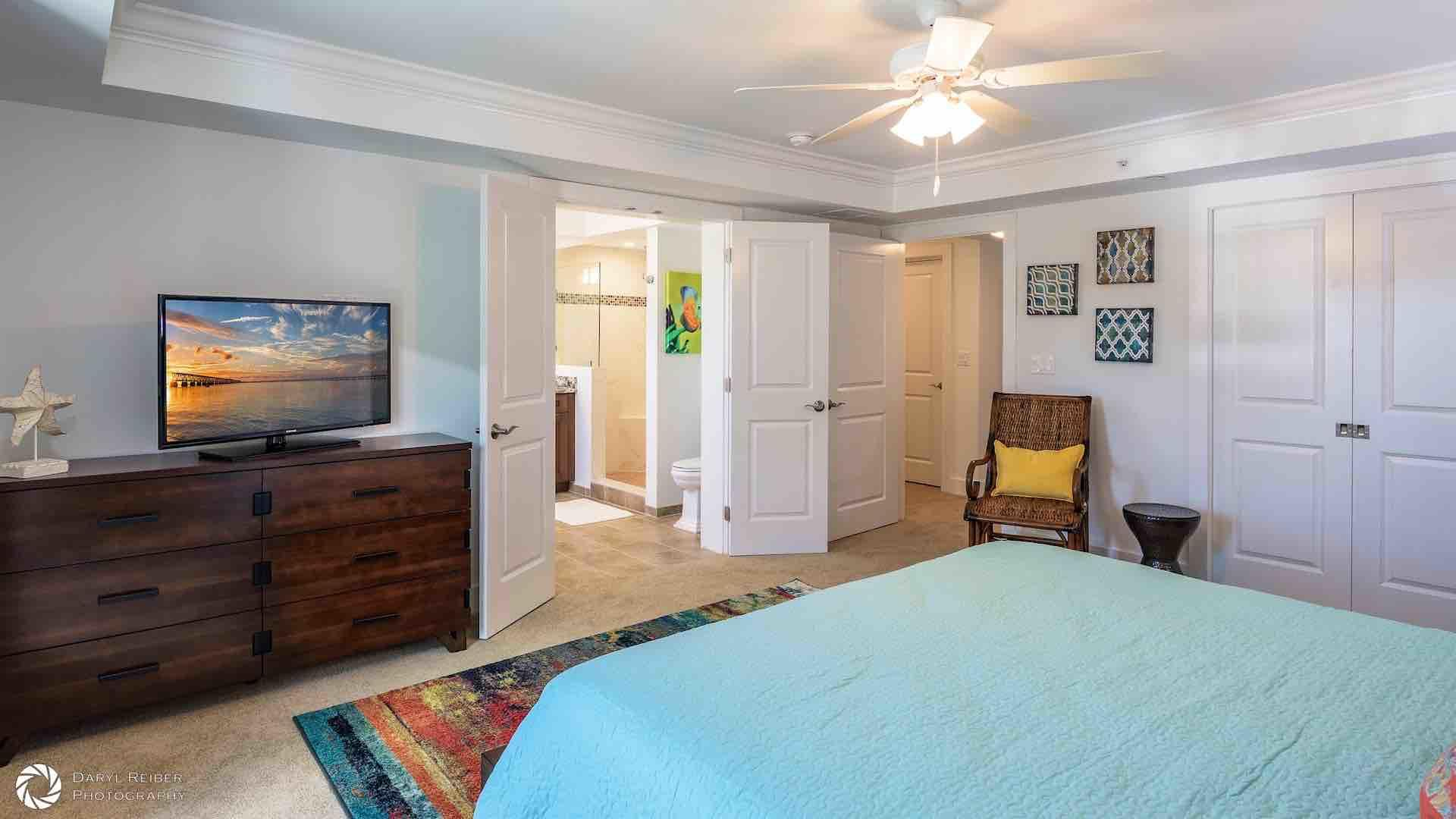 The first master suite has a large flat screen TV and an overhead fan...