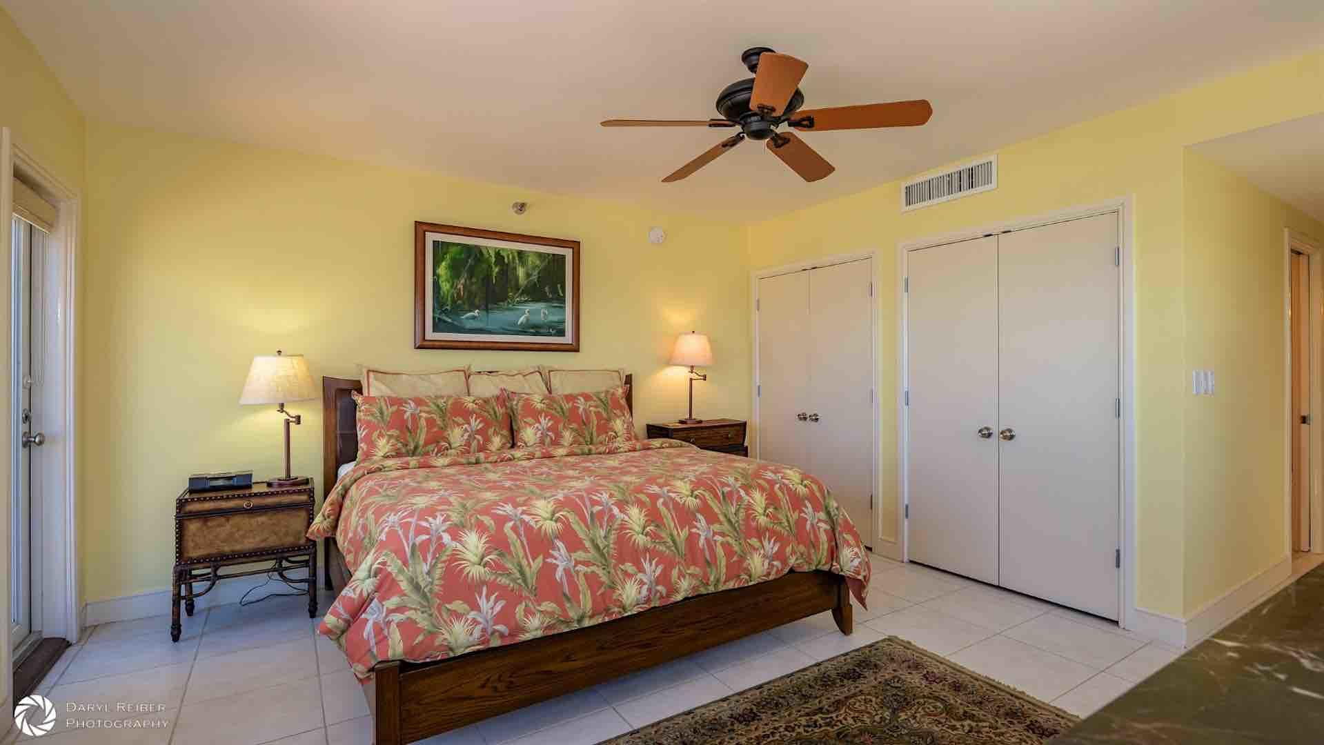 The spacious master bedroom has an overhead fan...