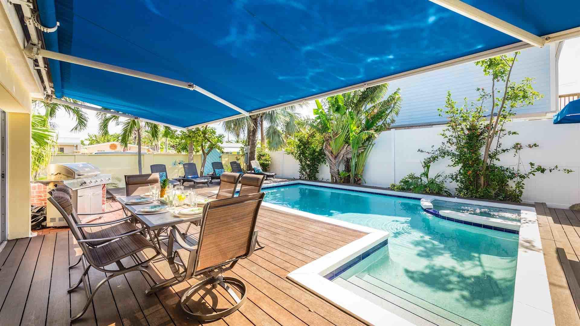 There is a shaded outdoor dining set for enjoying a poolside meal...
