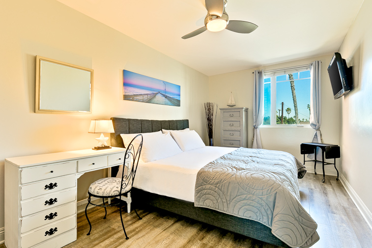 Queen bedroom with flat screen TV and a ceiling fan for your comfort.