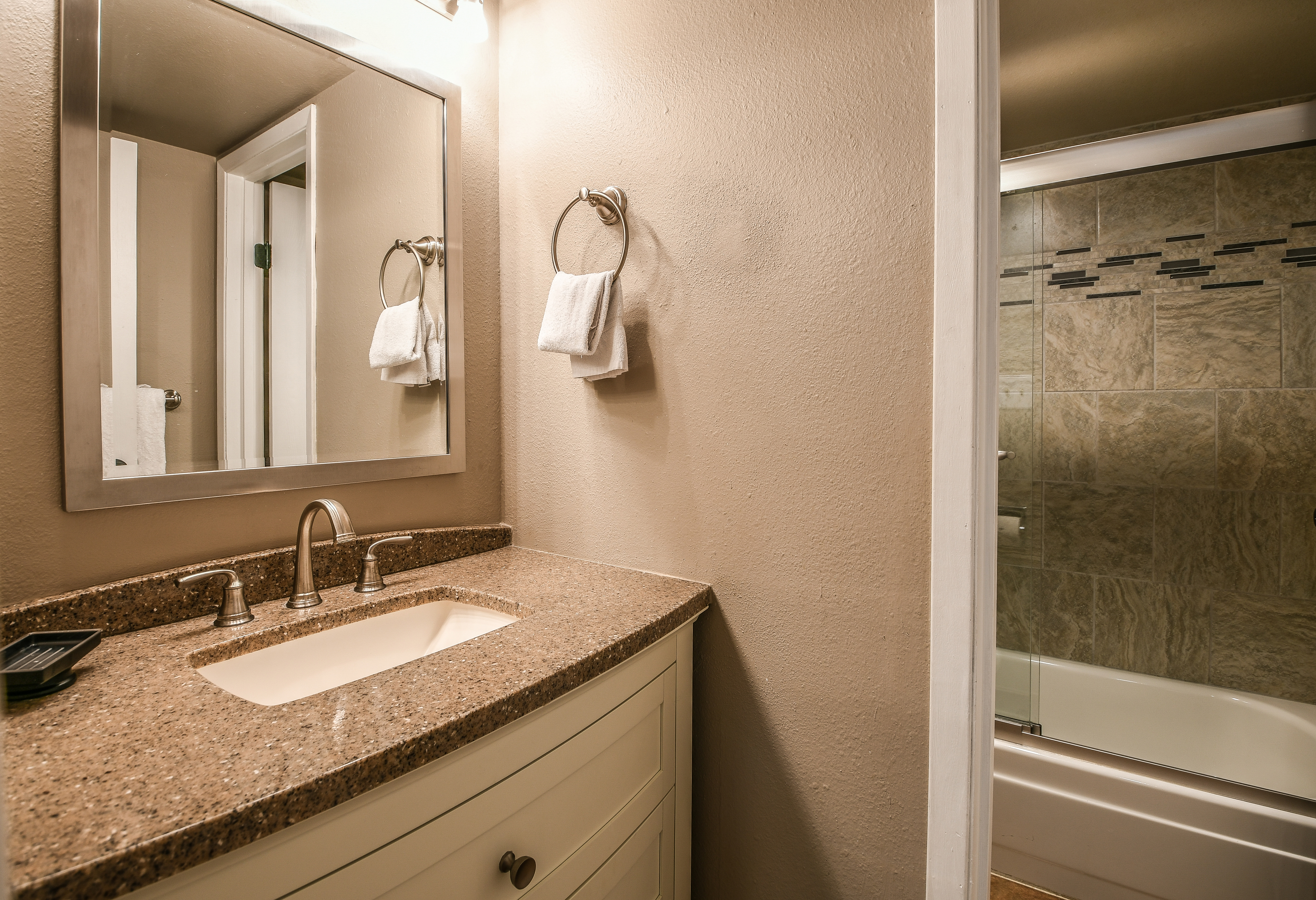 Bathroom with relaxing shower and sink with storage