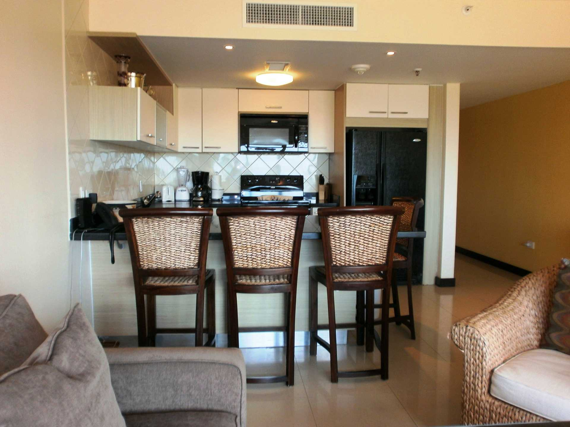 Full-sized fully equipped modern kitchen with 4-bar seat