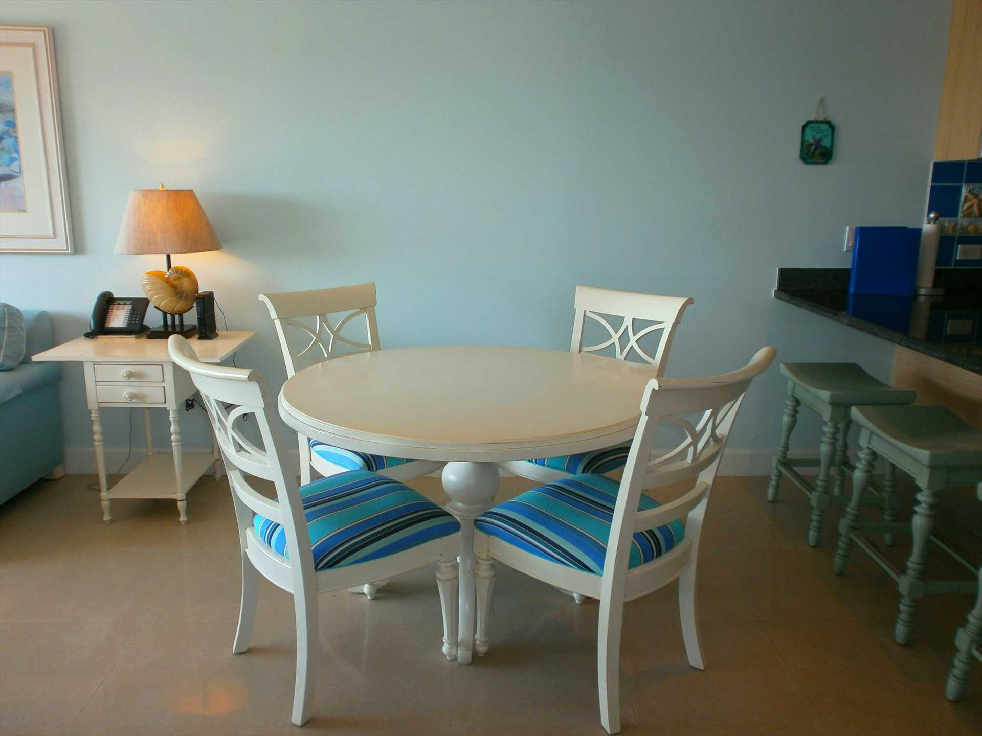 Dining area with 4-seat round table and 3-seat bar-table.