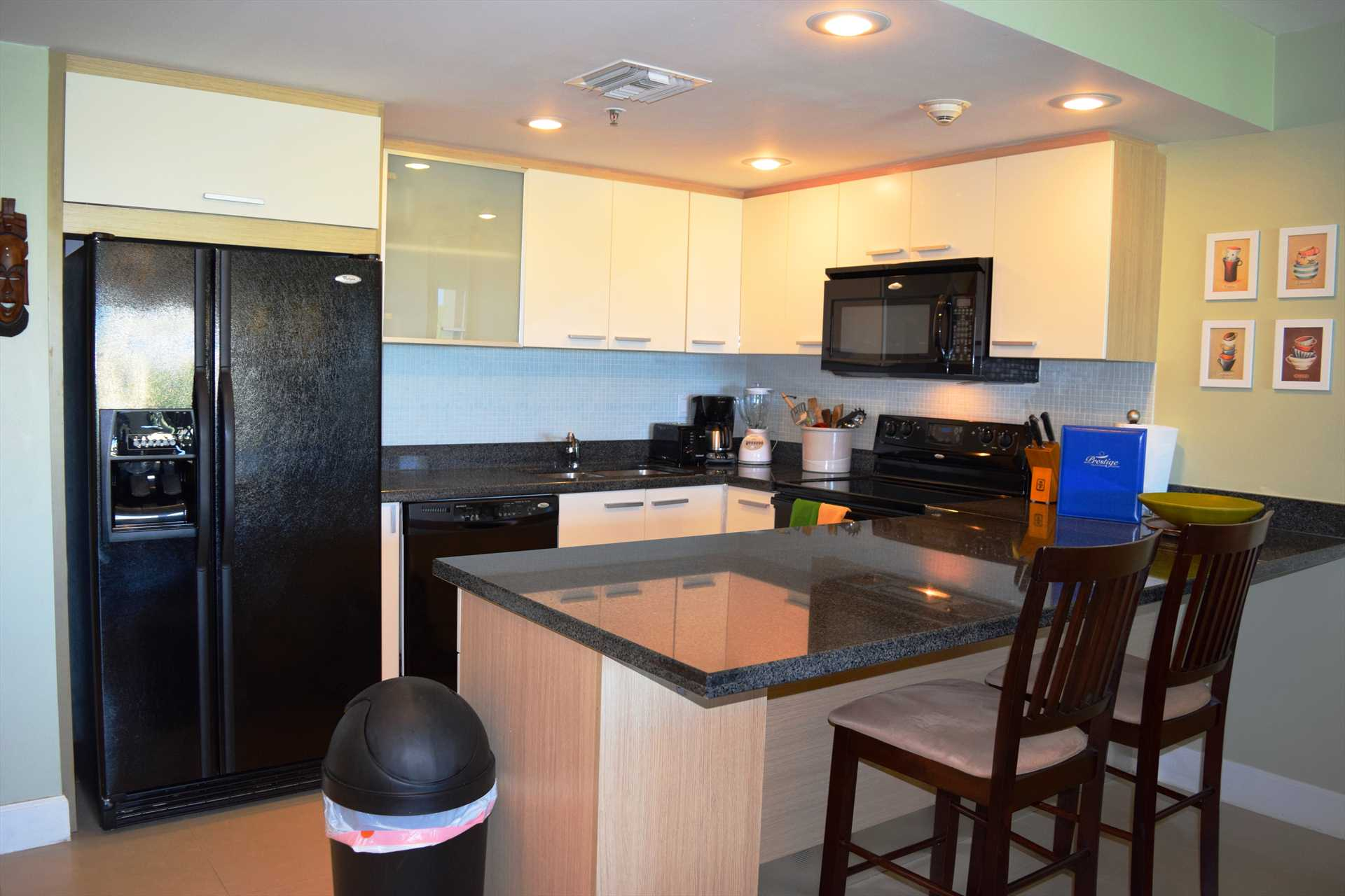 Full-sized fully equipped modern kitchen with 2-bar stools