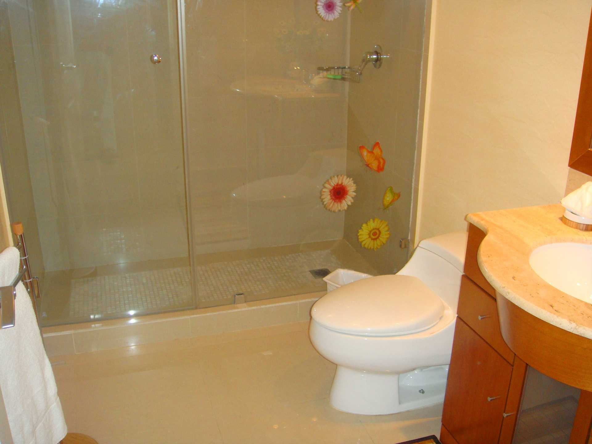 All three bathrooms are spacious and have glass door enclosed showers.