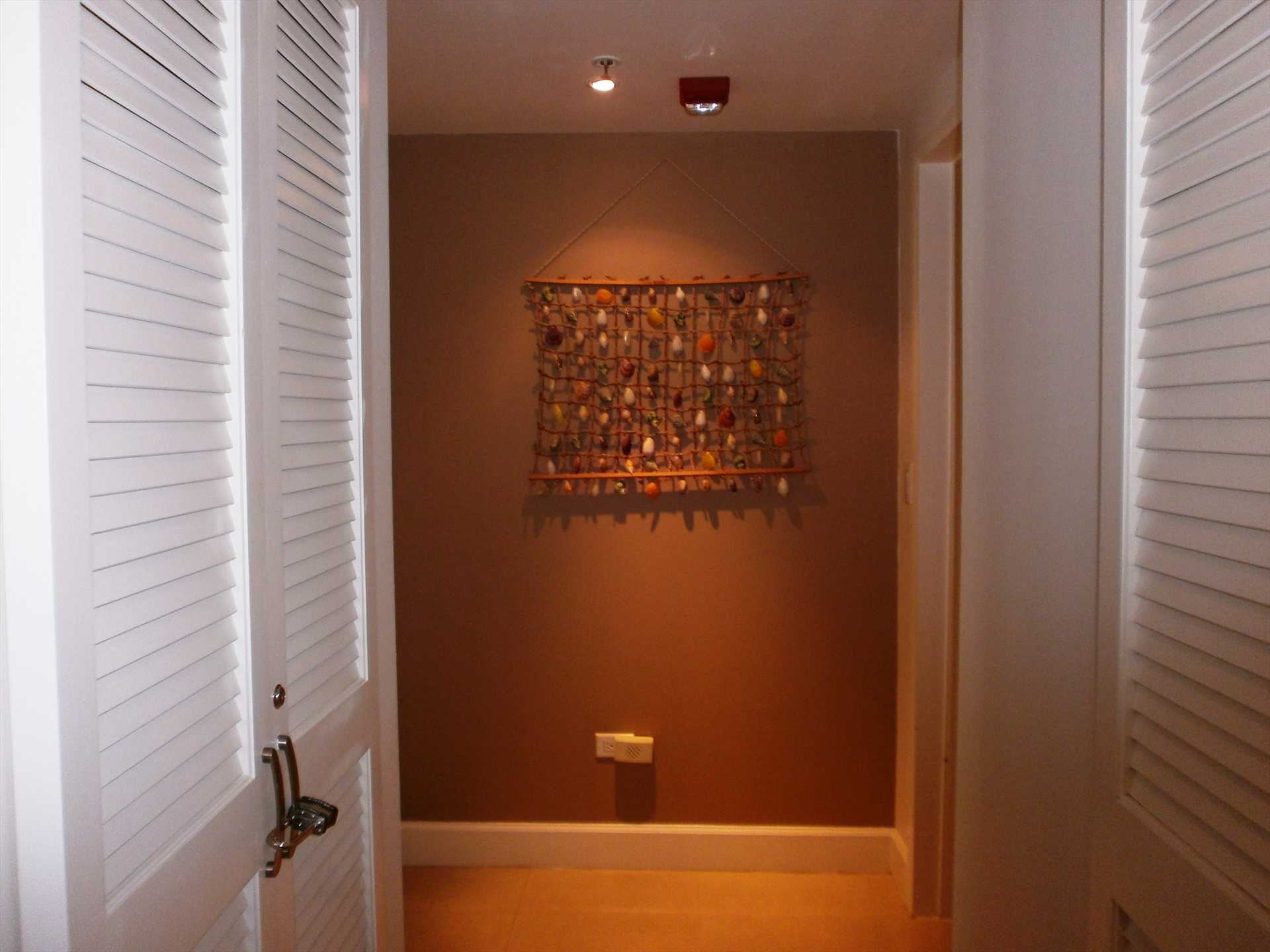 Corridor that lends access to laundry facilities, third bathroom and bedrooms