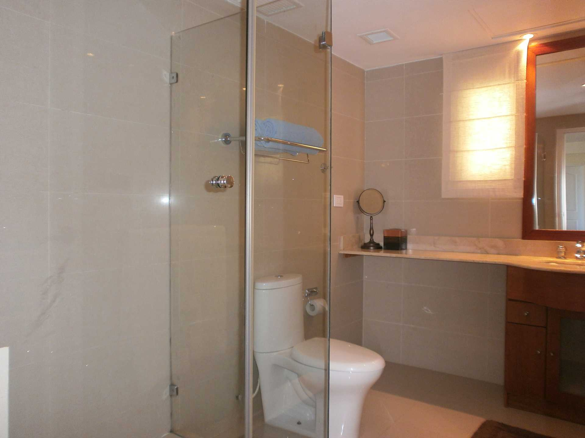 A second modern full bathroom with glass-enclosed shower area.     A second modern full bathroom with glass-enclosed shower area.