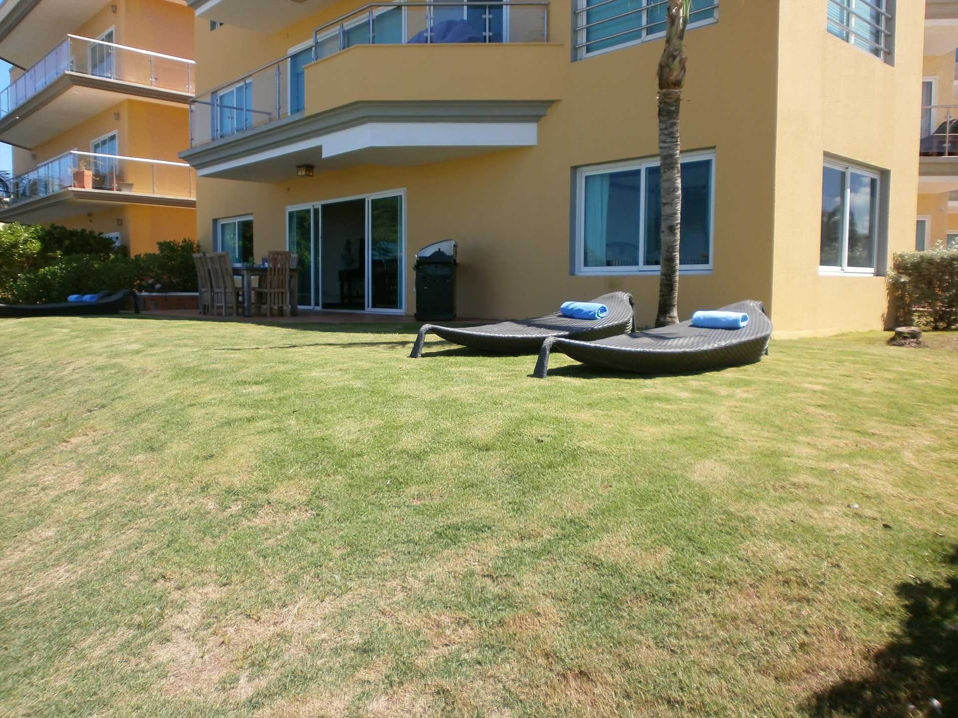 Private patio and garden with outdoor furniture and BBQ grill
