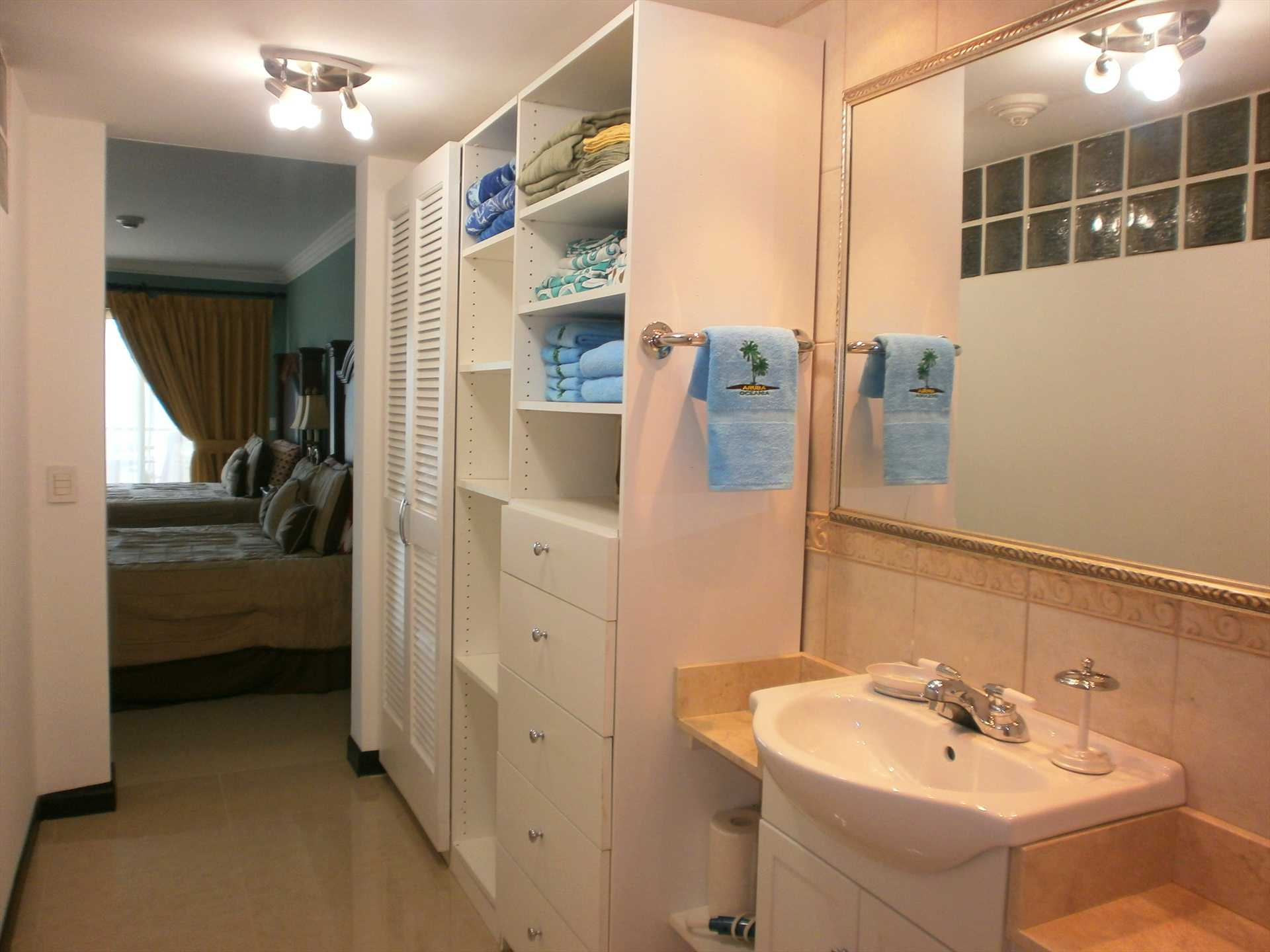 Master 'en suit' bathroom with two sinks, toilet, bidet and glass-enclosed shower.