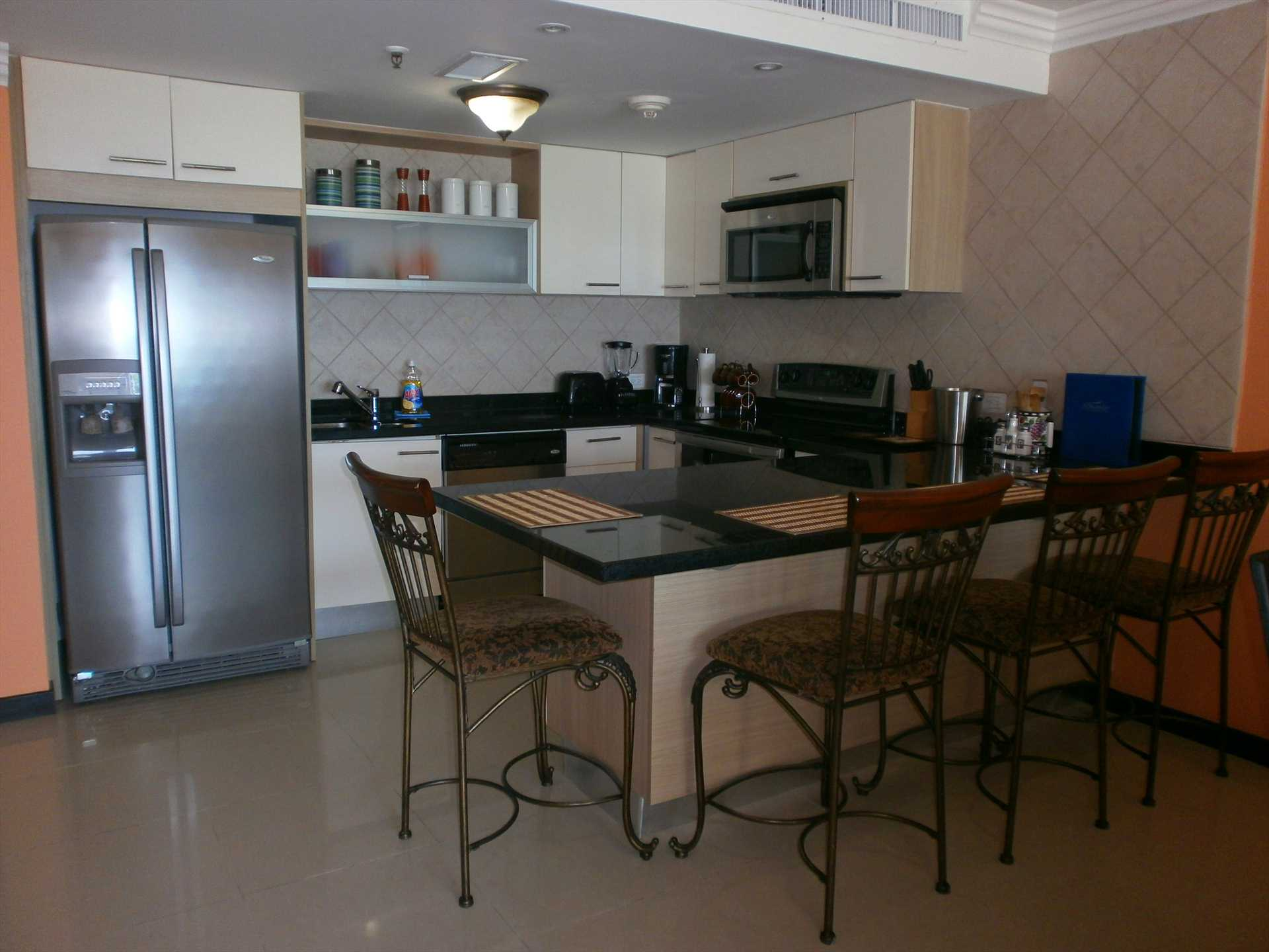A full-size fully equipped modern kitchen with 4-seat breakfast/bar table.