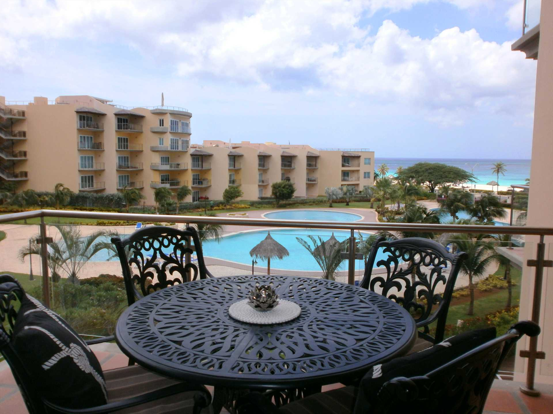 Balcony with 4-seat dinning table and amazing view of the pools and ocean