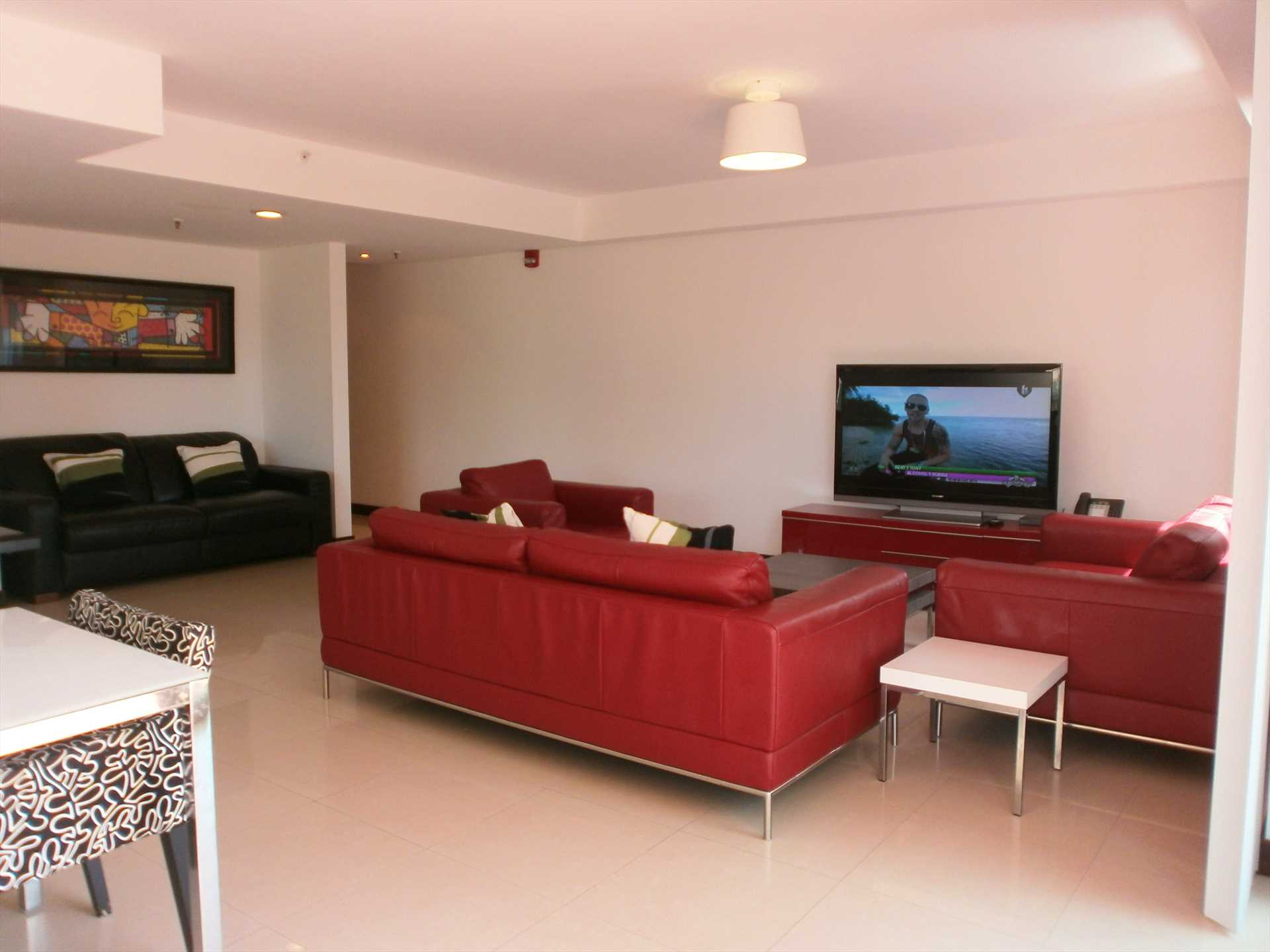 Living area with a large 4 piece sofa set and flatscreen HDTV.