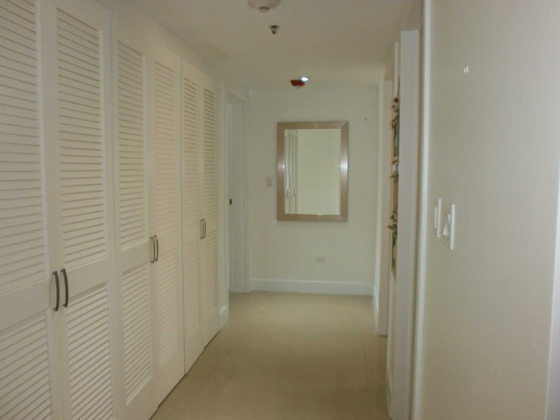Wide corridor with full laundry facility lends access to bedrooms.