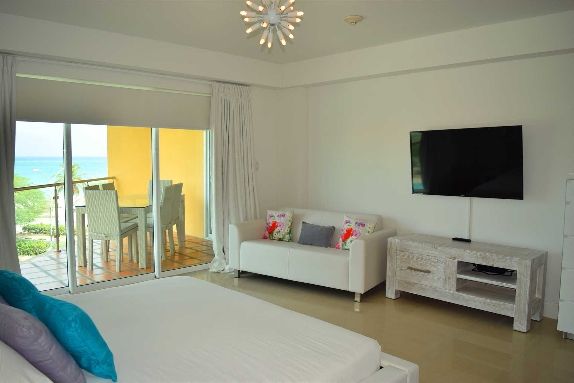 HDTV in master bedroom with sofa and access to balcony