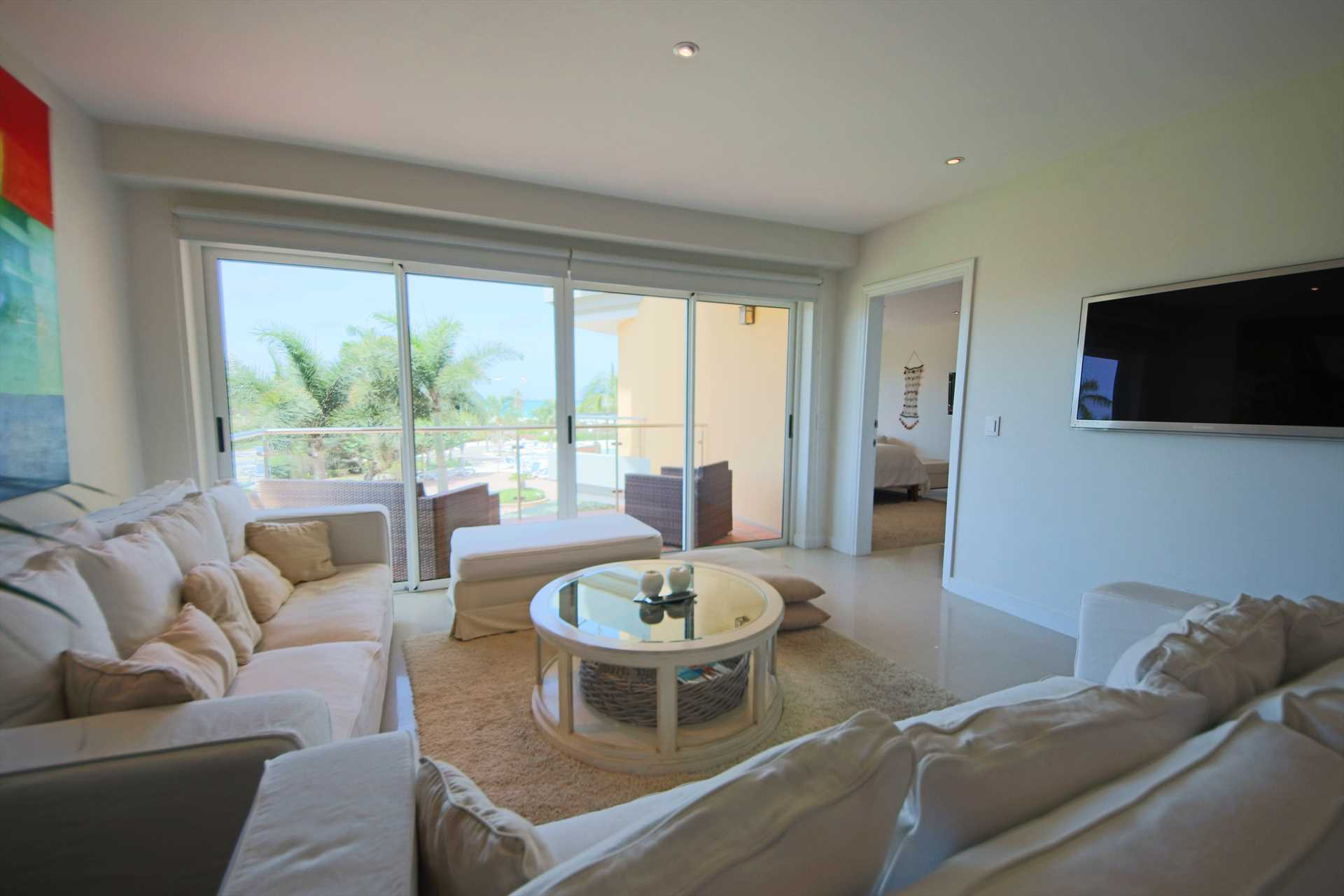 Living area with 2 sofas, HDTV and access to balcony with view
