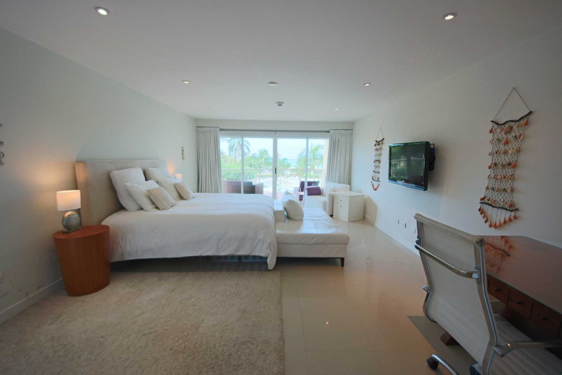 Master bedroom with a king-size bed, desk, HDTV and private balcony