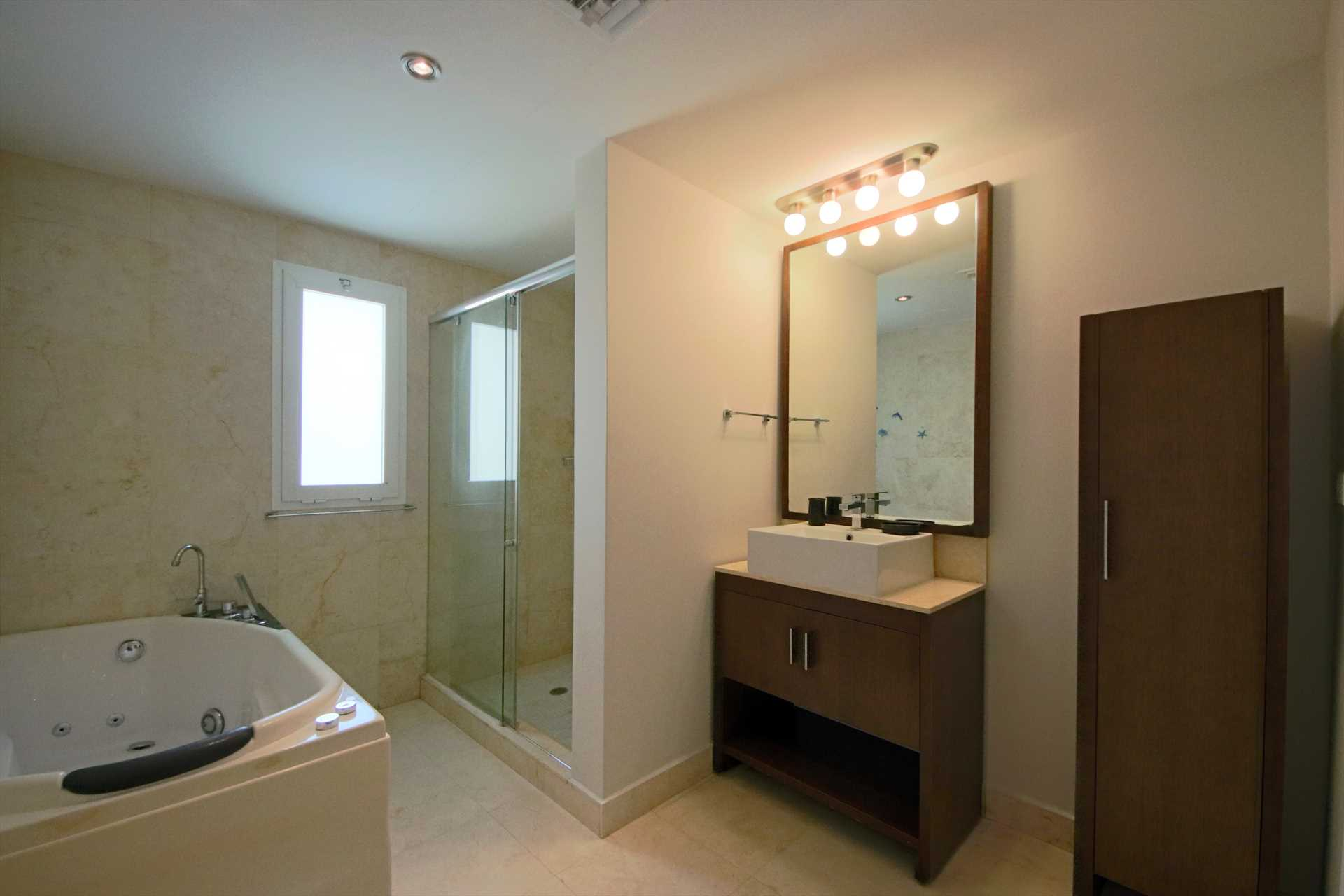 Master bedroom en-suite bathroom with shower and a jetted tub