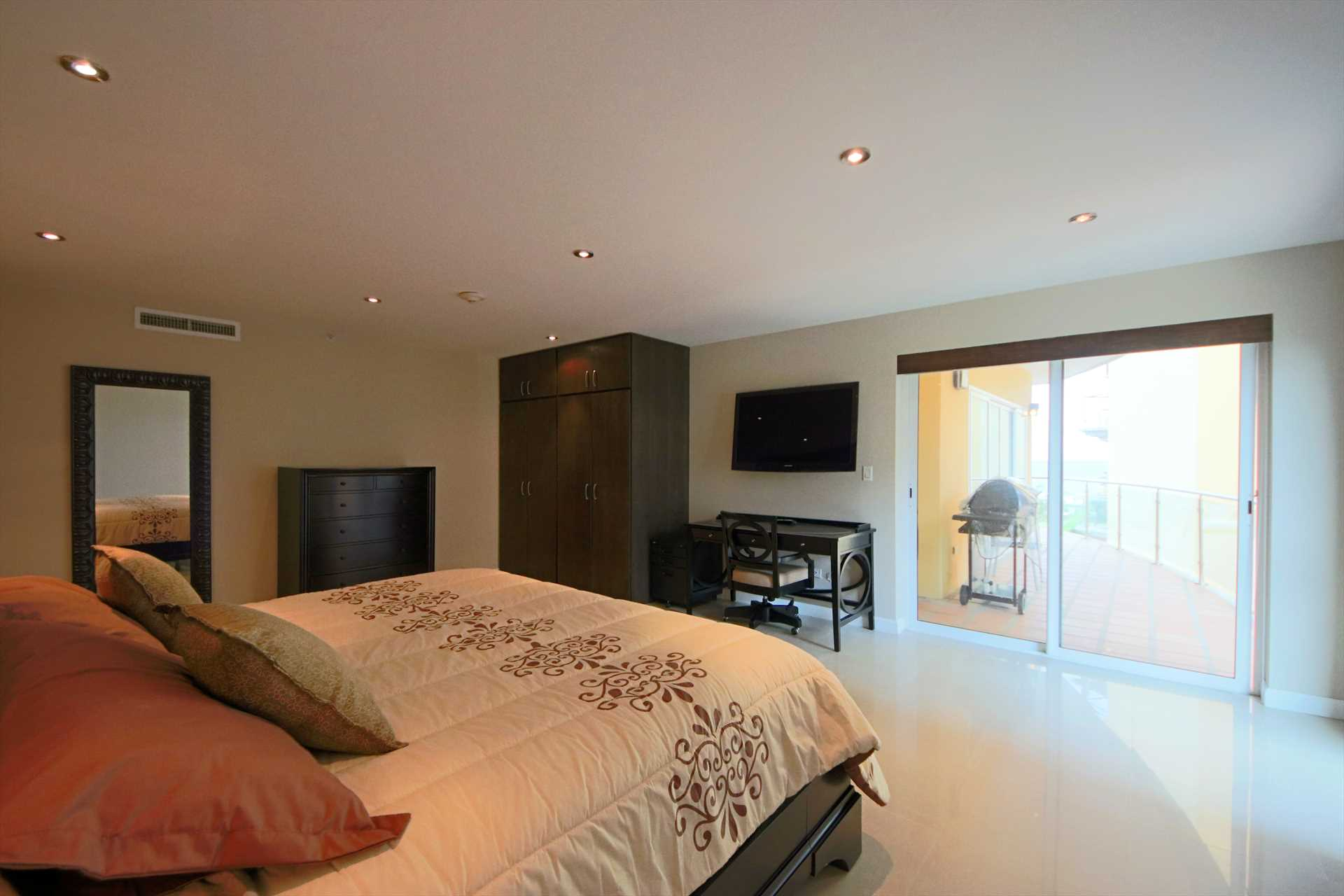 Master bedroom with TV and access to the balcony