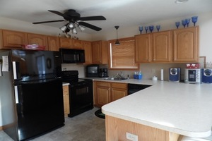 Kitchen with black appliances L shaped counters with ceiling fan