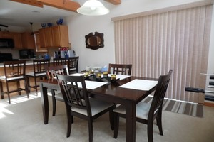 Dark Brown wooden Dinning room table with light above.