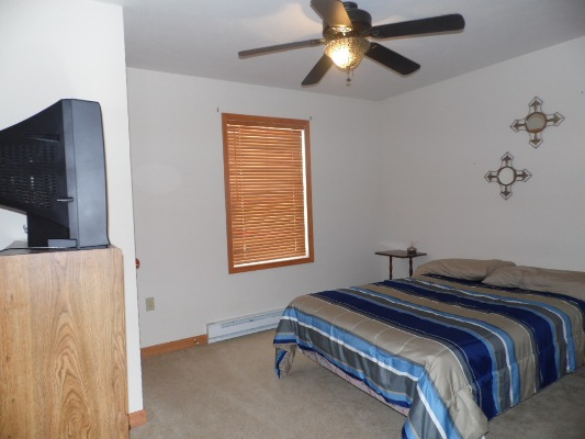 Bedroom with queen size bed with TV and ceiling fan