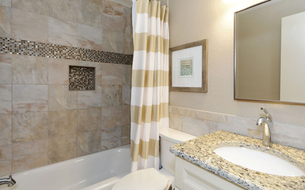 The bathroom with tub/shower combo.