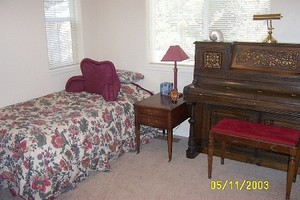Third bedroom with twin beds and antique piano.