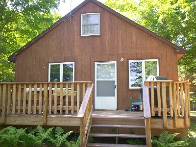 Cabin has beautiful deck with picnic table, chairs and grill