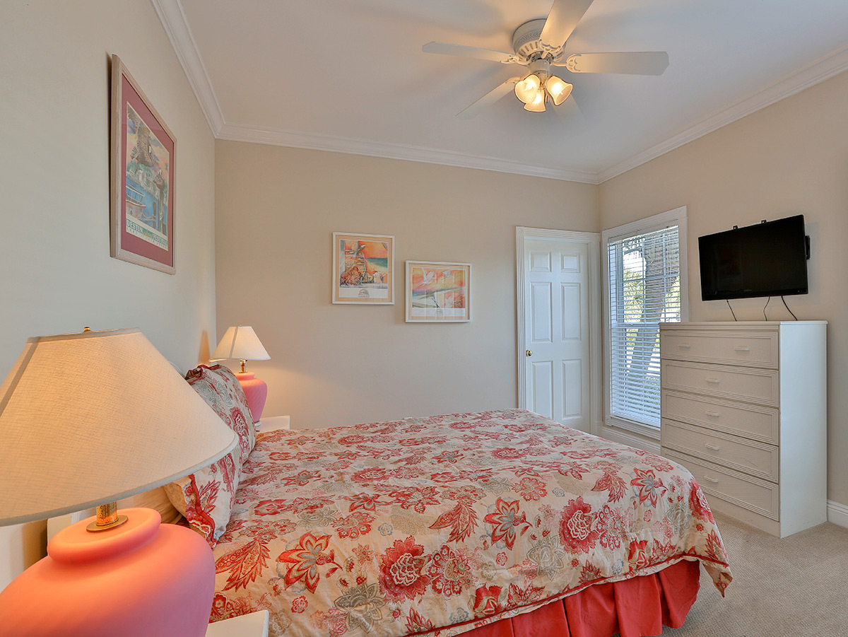 Bedroom with queen size bed and white dresser with TV.  Bedroom has a white ceiling fan