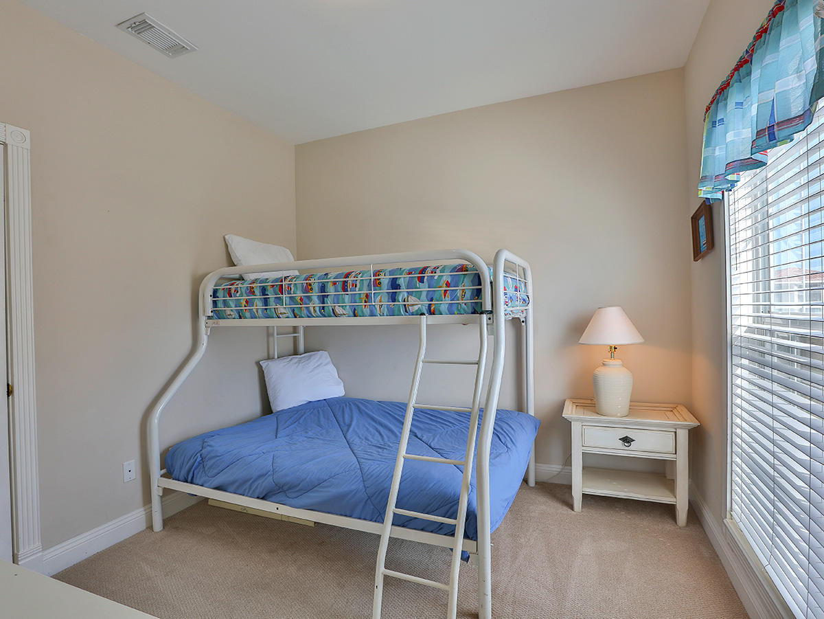 Bedroom has bunk beds  with night stand and lamp.  Seaspray9 - Destin FL