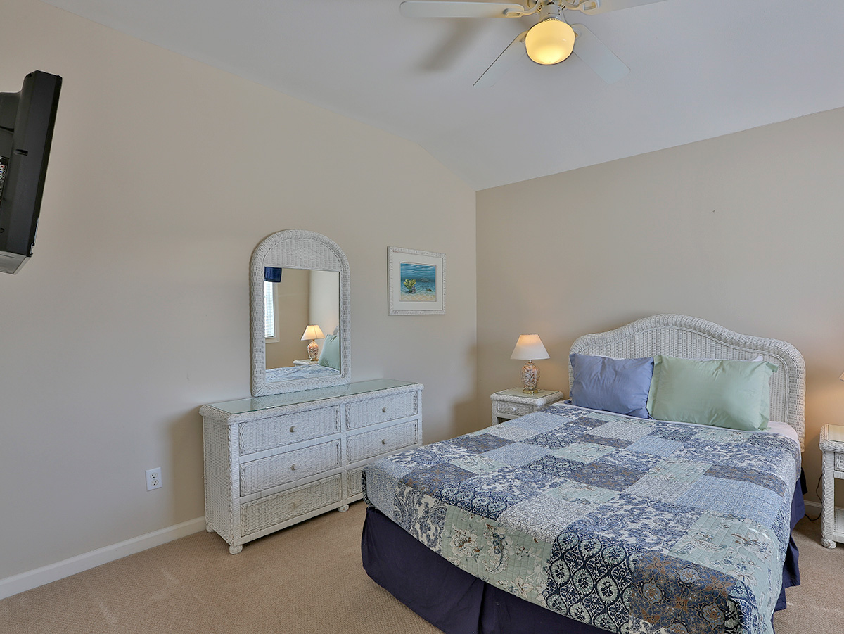 Queen size bed with white dresser and mirror - TV mounted on the wall  - Seaspray 9 Beach Fl