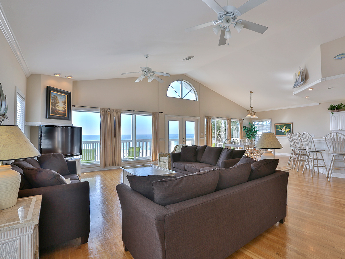Great dinning room with sofa and large tv with  two ceiling fans -