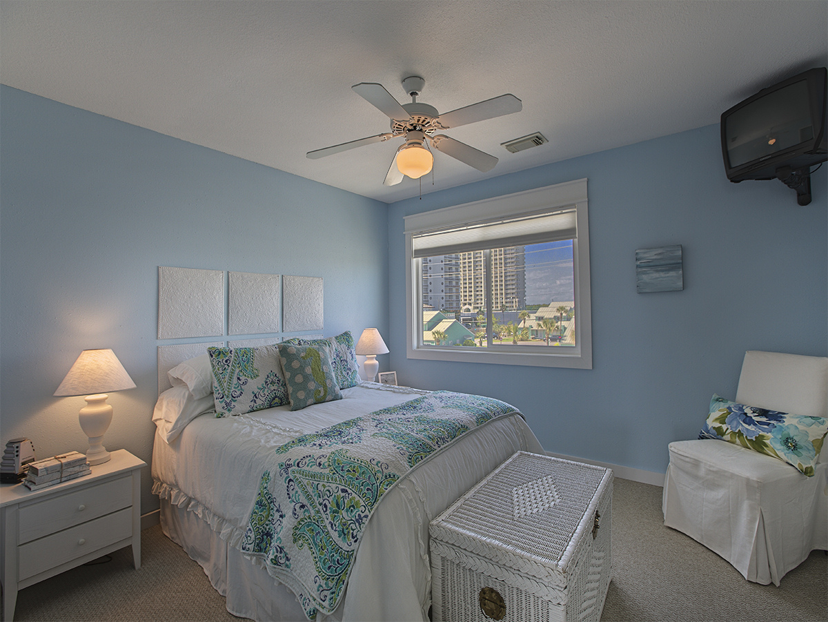 3rd Bedroom with ceiling fan - Queen size bed  with while coffee table and chair.