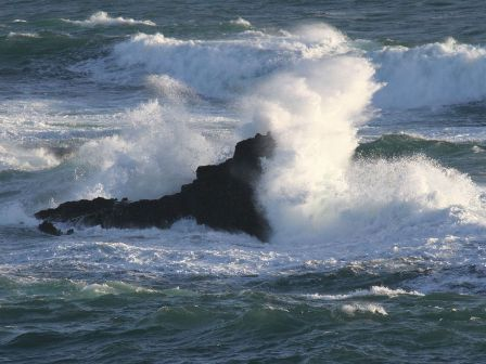 waves crashing on a rock in the ocean