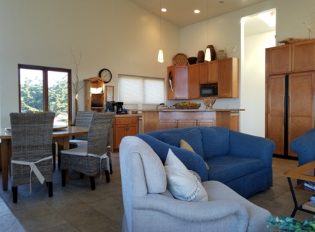 Great room seating, large round dining table, and kitchen.