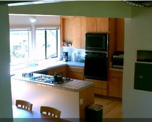 Bright, open kitchen, 5 burner gas range off dining area.