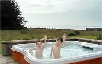 Oversized hot tub with meadow and ocean views.
